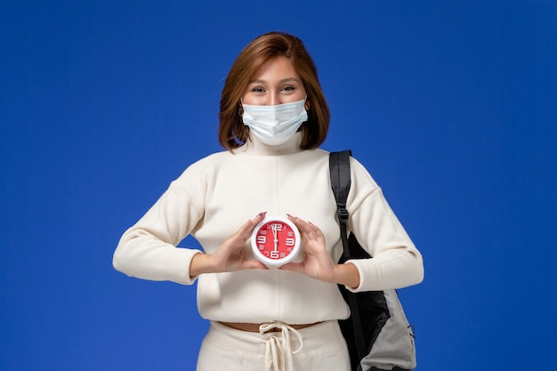 Front view young female student in white jersey wearing mask and holding clock and smiling on blue wall
