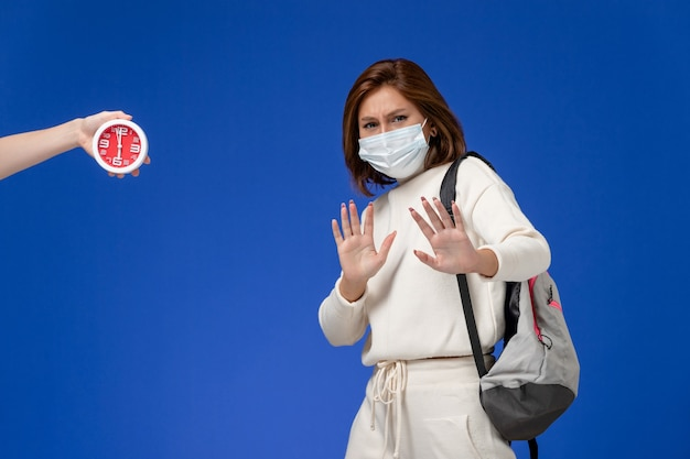 Front view young female student in white jersey wearing mask scared of female with clock on blue wall
