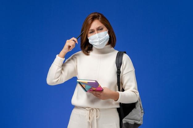 Vista frontale giovane studentessa in maglia bianca che indossa la maschera con borsa e quaderno sulla parete blu