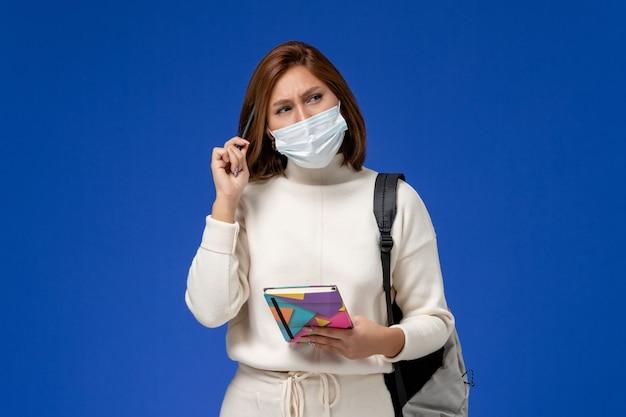 Vista frontale giovane studentessa in maglia bianca che indossa la maschera con borsa e quaderno pensando sulla parete blu