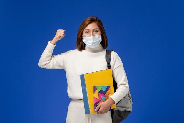 Vista frontale giovane studentessa in maglia bianca che indossa la maschera con borsa e quaderni sulla parete blu