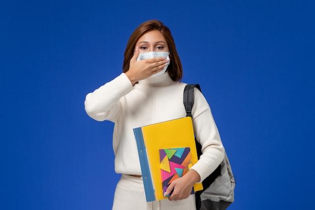 Vista frontale giovane studentessa in maglia bianca che indossa la maschera con borsa e quaderni chiudendo la bocca sulla parete blu