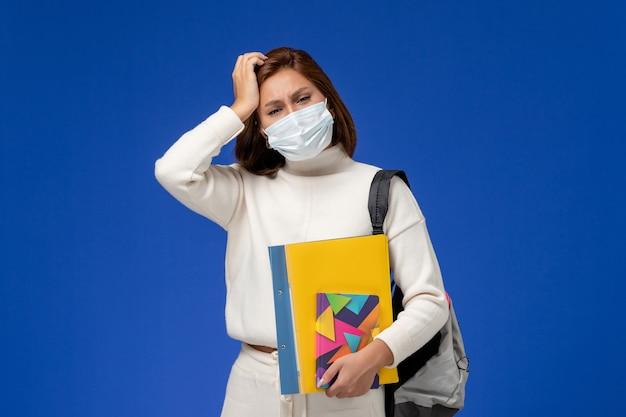 Vista frontale giovane studentessa in maglia bianca che indossa la maschera con borsa e quaderni che hanno mal di testa sulla parete blu