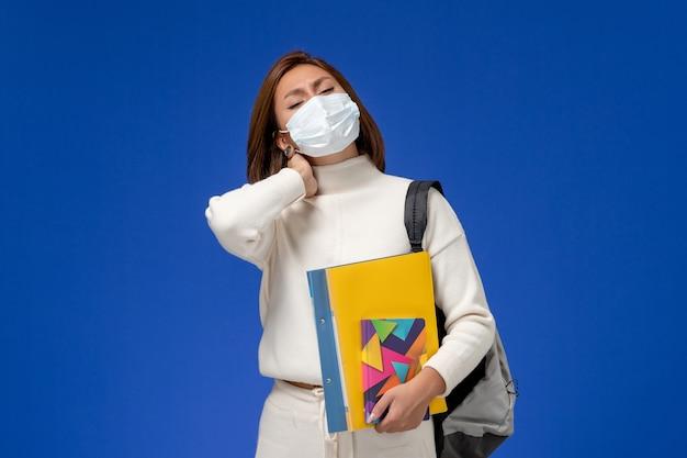 Vista frontale giovane studentessa in maglia bianca che indossa la maschera con borsa e quaderni con mal di testa sulla parete blu