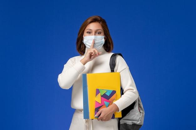 Vista frontale giovane studentessa in maglia bianca che indossa la maschera con borsa e quaderni che mostra il segno di silenzio sulla parete blu