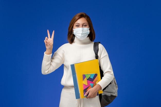 Vista frontale giovane studentessa in maglia bianca che indossa la maschera con borsa e quaderni che mostra il segno di vittoria sulla parete blu
