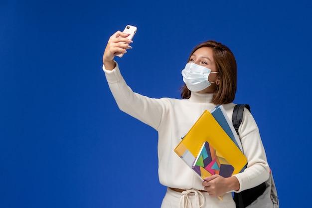 Vista frontale giovane studentessa in maglia bianca che indossa la maschera con borsa e quaderni e prendendo un selfie sulla parete blu