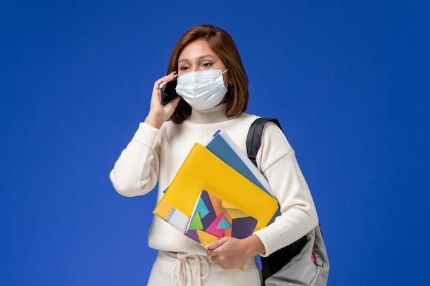 Vista frontale giovane studentessa in maglia bianca che indossa la maschera con borsa e quaderni parlando al telefono sulla parete blu
