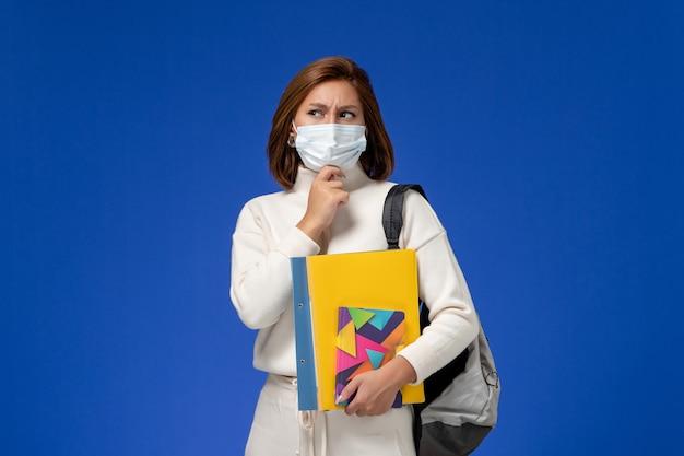 Vista frontale giovane studentessa in maglia bianca che indossa la maschera con borsa e quaderni pensando sulla parete blu