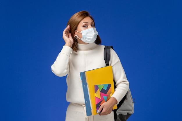 Vista frontale giovane studentessa in maglia bianca che indossa la maschera con borsa e quaderni cercando di ascoltare sulla parete blu