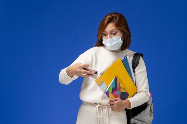 Vista frontale giovane studentessa in maglia bianca che indossa la maschera con borsa e quaderni e utilizzando il suo telefono sulla parete blu