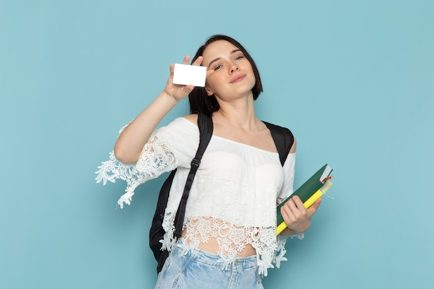 Front view young female student in white shirt blue jeans and black bag holding copybooks and card on the blue space female student university teach