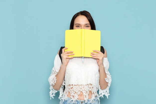 Giovane studentessa di vista frontale in blue jeans della camicia bianca e borsa nera che tiene il quaderno giallo sulla scuola dell'università della studentessa dello spazio blu