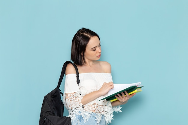 Front view young female student in white shirt blue jeans and black bag reading copybook on the blue space female student  girl