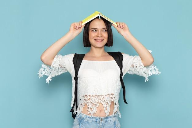 Giovane studentessa di vista frontale in blue jeans della camicia bianca e borsa nera che sorride e che si diverte sulla scuola dell'università della studentessa dello spazio blu
