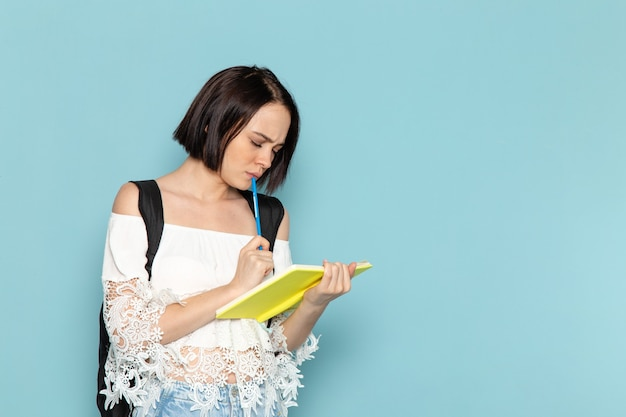 Front view young female student in white shirt blue jeans and black bag writing down notes on the blue space student university school