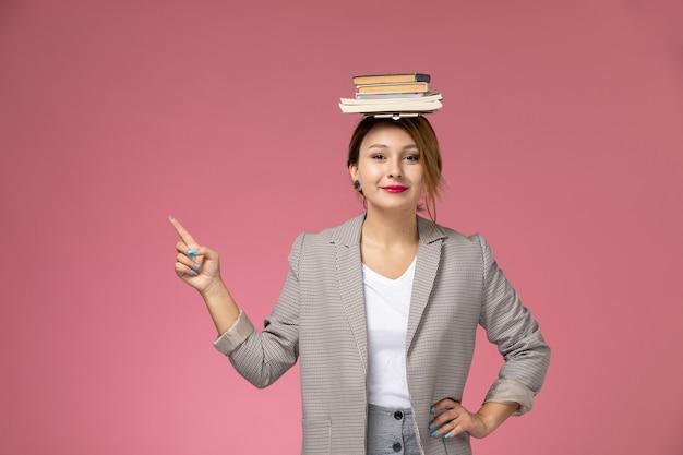 Vista frontale giovane studentessa in t-shirt bianca cappotto grigio e pantaloni grigi con libri sulla sua testa sullo sfondo rosa lezioni di studio universitario