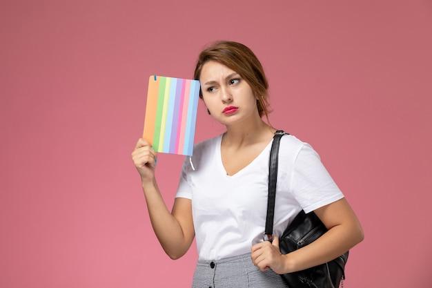 Giovane studentessa di vista frontale in maglietta bianca e pantaloni grigi con il quaderno nelle sue mani pensando sull'istituto universitario di lezioni di sfondo rosa