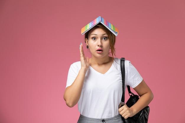 Vista frontale giovane studentessa in t-shirt bianca e pantaloni grigi con il quaderno sulla sua testa su sfondo rosa studente lezioni universitarie