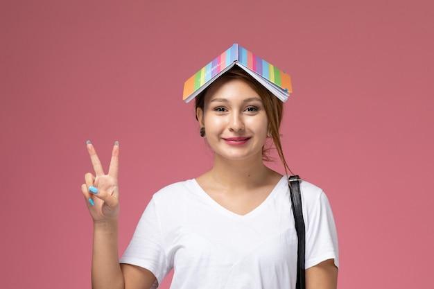 Vista frontale della giovane studentessa in maglietta bianca e pantaloni grigi con il sorriso del quaderno e il gesto di vittoria su sfondo rosa, lezioni di studente universitario