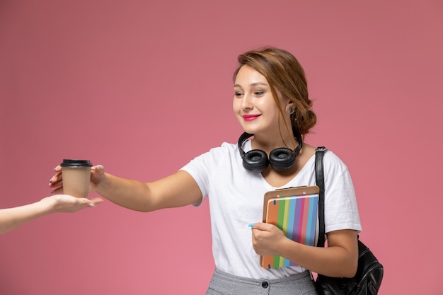 Front view young female student in white t-shirt and grey trousers with earphones holding coffee cup on pink background student lessons university college
