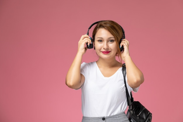 Front view young female student in white t-shirt and grey trousers with earphones on pink background student lessons university college