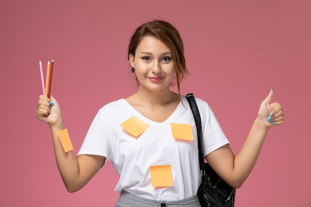 Front view young female student in white t-shirt smiling holding pencils on the pink background lessons university college study