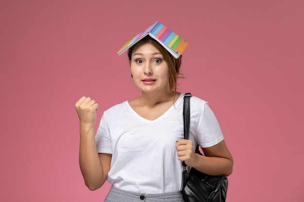 Front view young female student in white t-shirt with copybook and bag posing on the pink background lesson university college study book