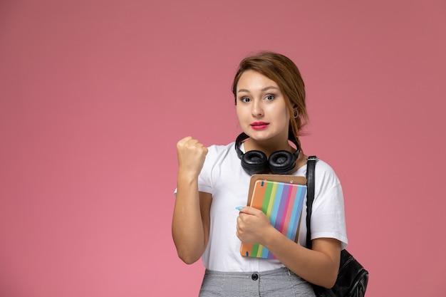 Giovane studentessa di vista frontale in maglietta bianca con gli auricolari del quaderno e la borsa in posa sul libro di studio di lezione universitaria di sfondo rosa