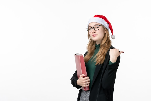 白い壁の本の学校の大学のファイルと正面図若い女子学生