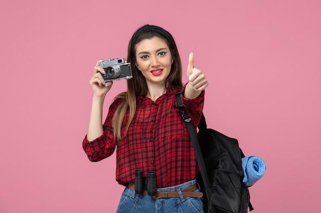 Vista frontale giovane femmina di scattare una foto con la fotocamera sullo sfondo rosa foto donna colore