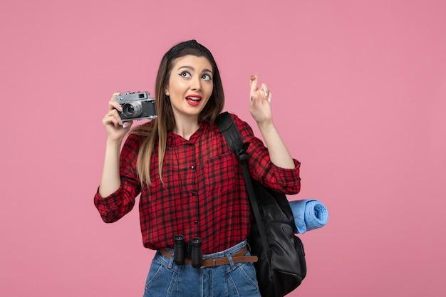 Giovane femmina di vista frontale che cattura maschera con la macchina fotografica sui colori della donna della foto del fondo rosa