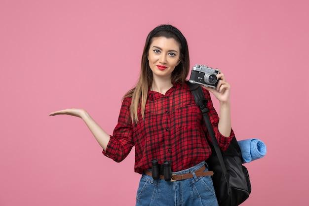 Giovane femmina di vista frontale che cattura maschera con la macchina fotografica sul modello rosa della foto della donna del fondo