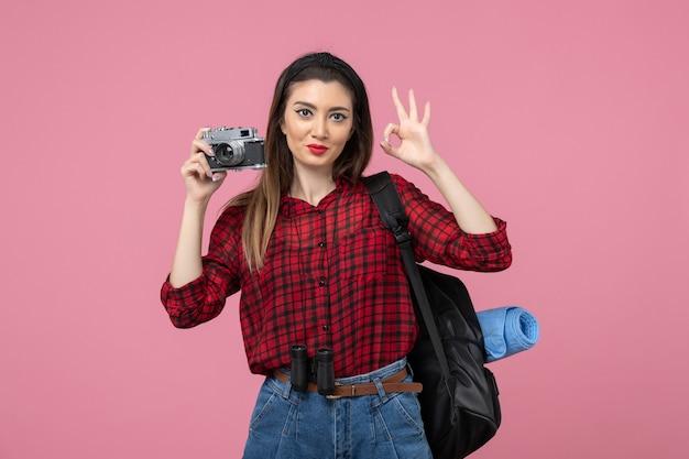 Giovane femmina di vista frontale che cattura maschera con la macchina fotografica sul colore rosa della donna della foto dello scrittorio