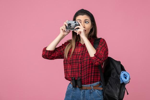 Giovane femmina di vista frontale che cattura maschera con la macchina fotografica sul colore rosa della foto della donna del pavimento