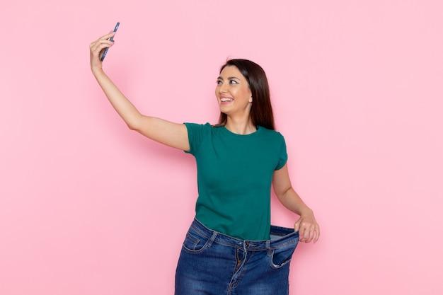 Вид спереди молодой женщины, делающей селфи на розовой стене, упражнения спорт, тренировка, талия, красота