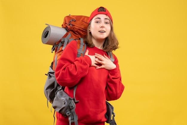 胸に手を置くバックパックと正面図若い女性観光客