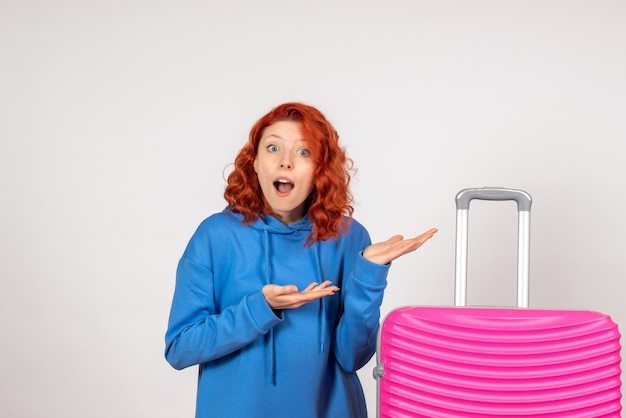 Vista frontale del giovane turista femminile con borsa rosa sulla parete chiara