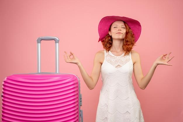 Vista frontale del giovane turista femminile con cappello rosa e borsa meditando sulla parete rosa