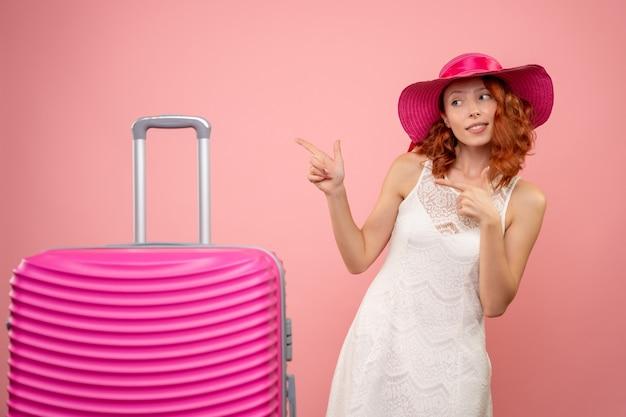 Vista frontale del giovane turista femminile con cappello rosa e borsa sulla parete rosa