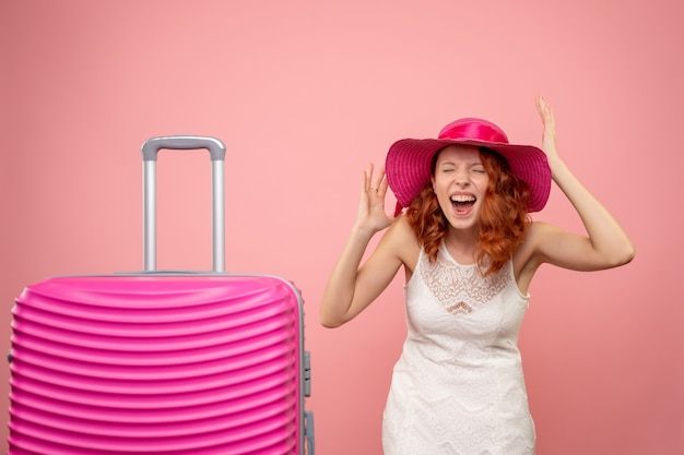 Front view of young female tourist with pink hat and bag rejoicing on pink wall