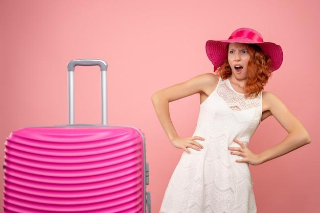 Vista frontale del giovane turista femminile con cappello rosa e borsa sorpreso sulla parete rosa