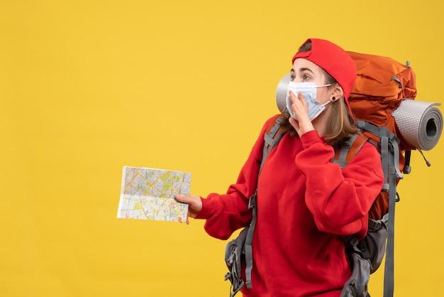 Вид спереди молодая женщина-путешественница с рюкзаком и маской, держащая карту путешествия