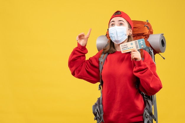 指を上に向けて旅行チケットを保持しているバックパックとマスクを持つ若い女性旅行者の正面図