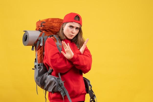 正面図バックパック交差手を持つ若い女性旅行者