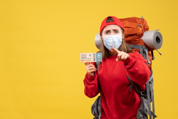 Front view young female traveler with backpack and mask holding ticket pointing finger up