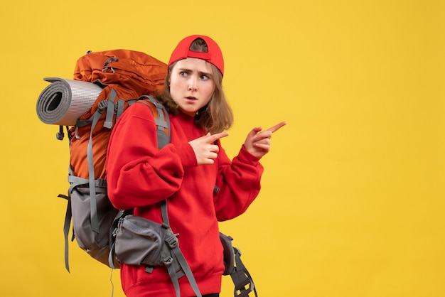 Front view young female traveler with backpack pointing finger right