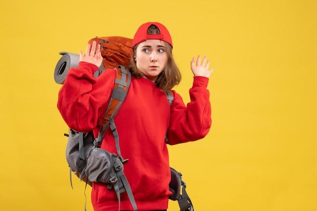 手を上げるバックパックと正面図若い女性旅行者
