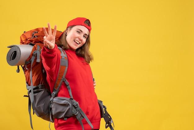 Giovane donna che viaggia da vista frontale con lo zaino che mostra tre dita