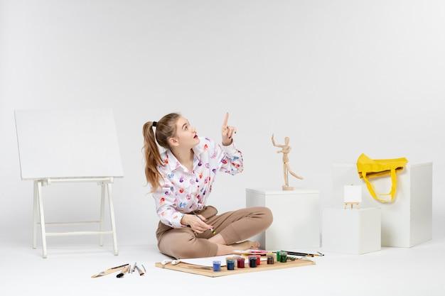 白い背景に描画しようとしている正面図若い女性